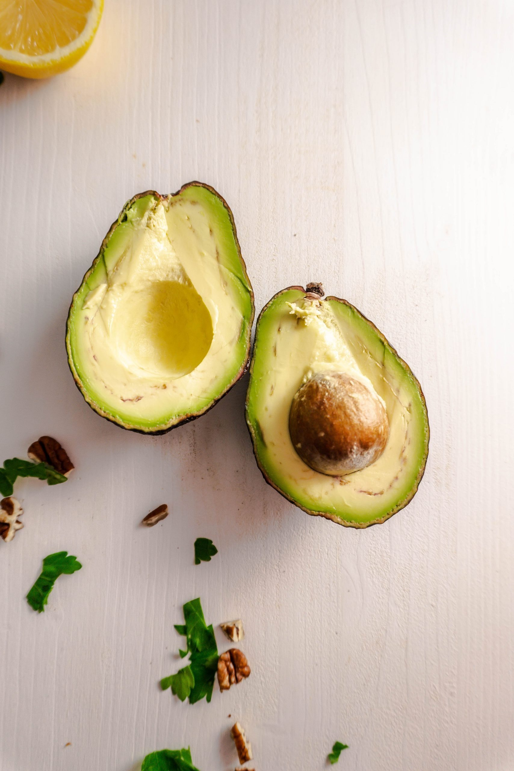 Two Avocados with chopped celery and pecans in the background photographed on a white surface