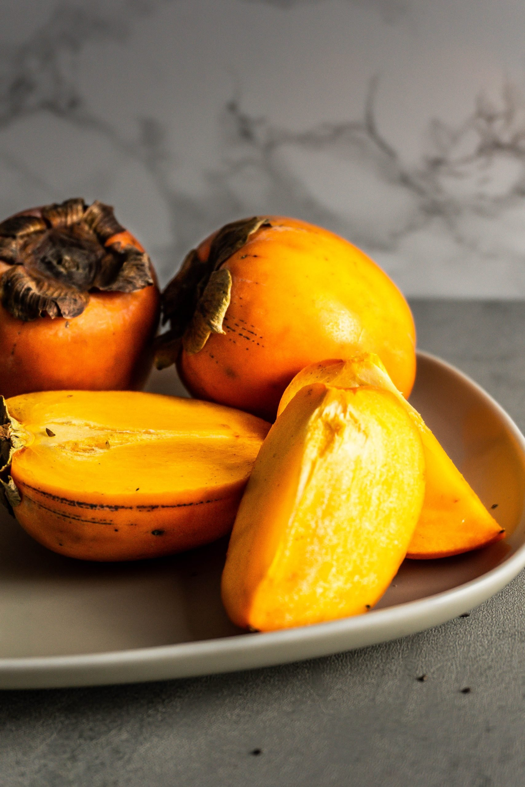 Persimmons whole and cut up on a plate