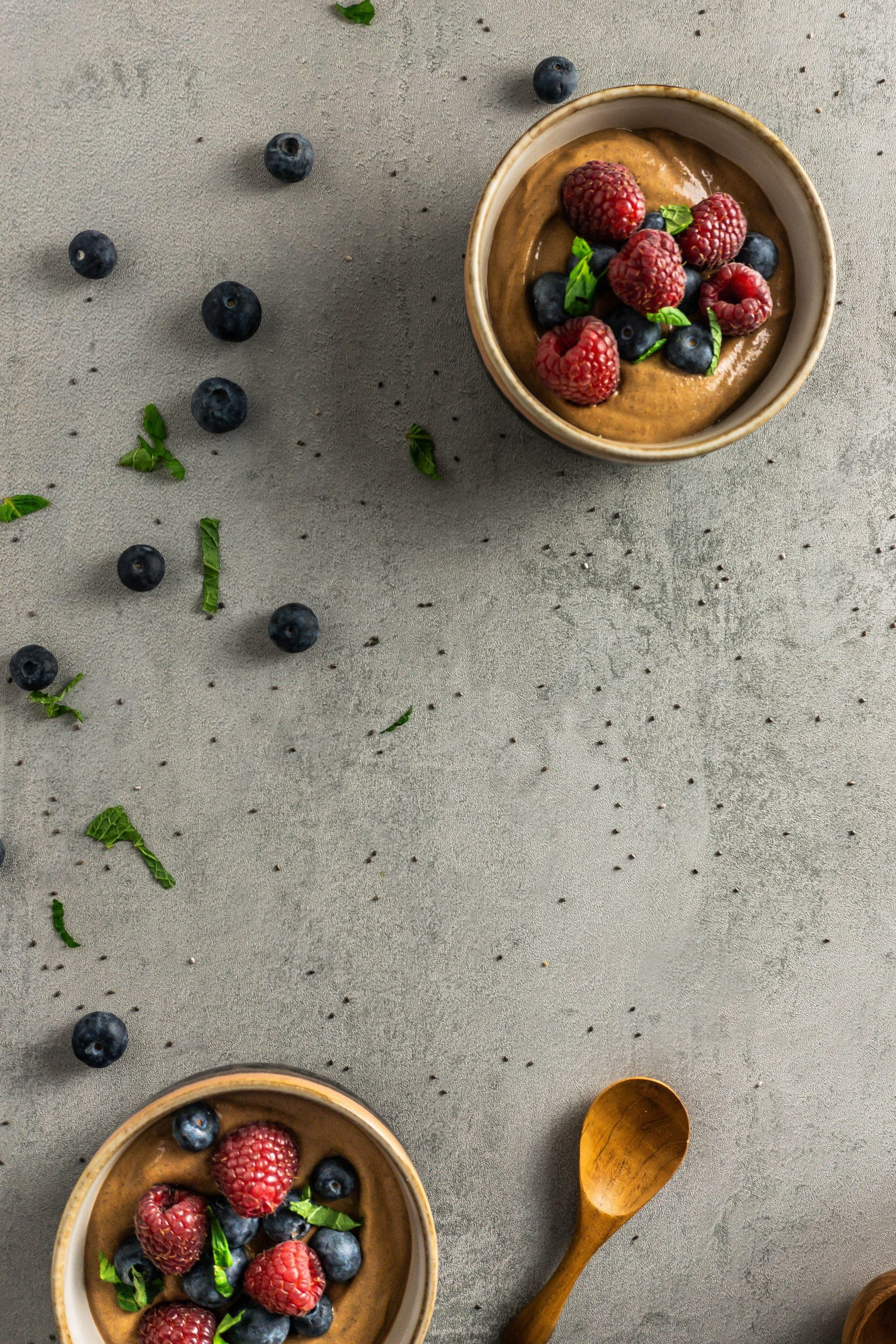 Chocolate Chia Seed Puddings in two bowls, topped with blueberries, raspberries, mint leaves. Photographed overhead on a grey background with blueberries, mint leaves, and chia seeds scattered around