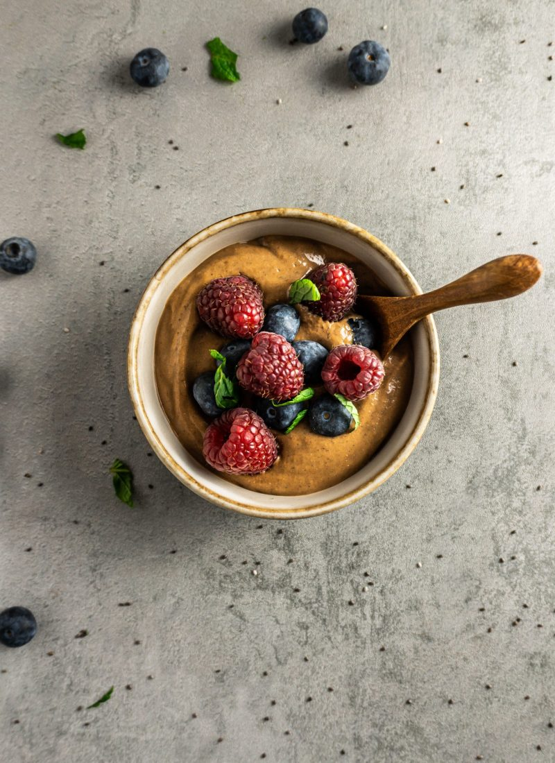 Chocolate Chia Seed Pudding in a bowl with a wooden spoon, topped with blueberries, raspberries, mint leaves. Photographed overhead on a grey background with blueberries, mint leaves, and chia seeds scattered around