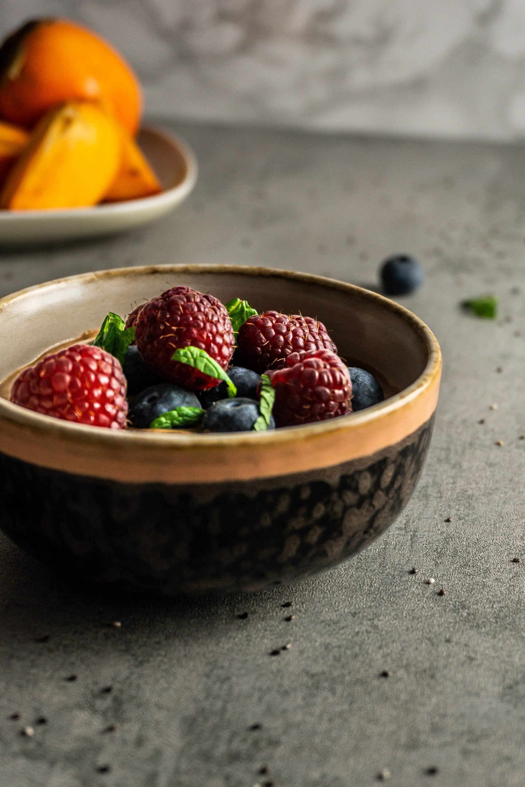 Chocolate Chia Seed Pudding in a bowl, topped with blueberries, raspberries, mint leaves. Photographed from a three-quarter angle with chia seeds scattered around and persimmons visible in the background