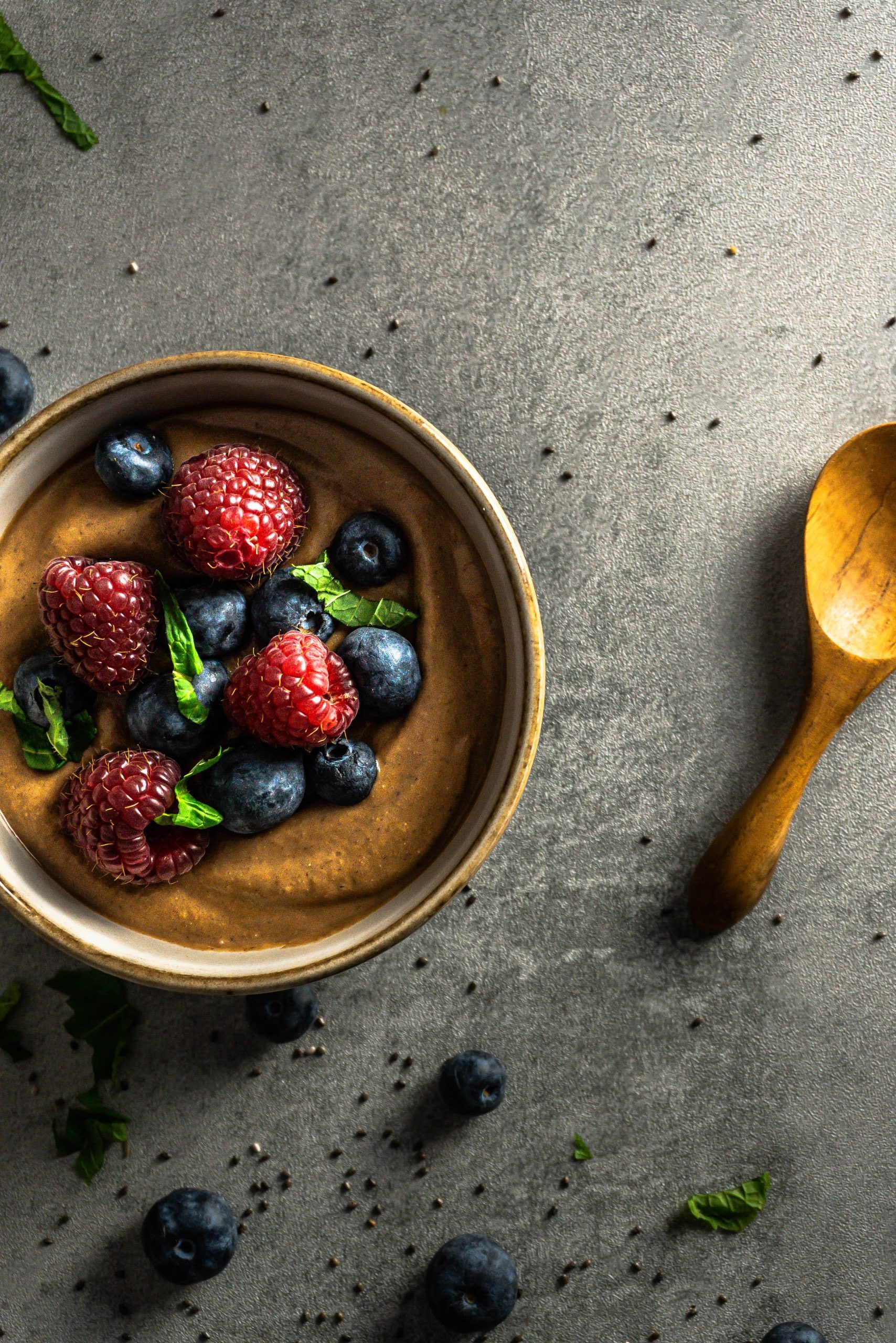 Chocolate Chia Seed Pudding in a bowl, topped with blueberries, raspberries, mint leaves. Photographed overhead on a grey background with blueberries, mint leaves, and chia seeds scattered and a wooden spoon visible