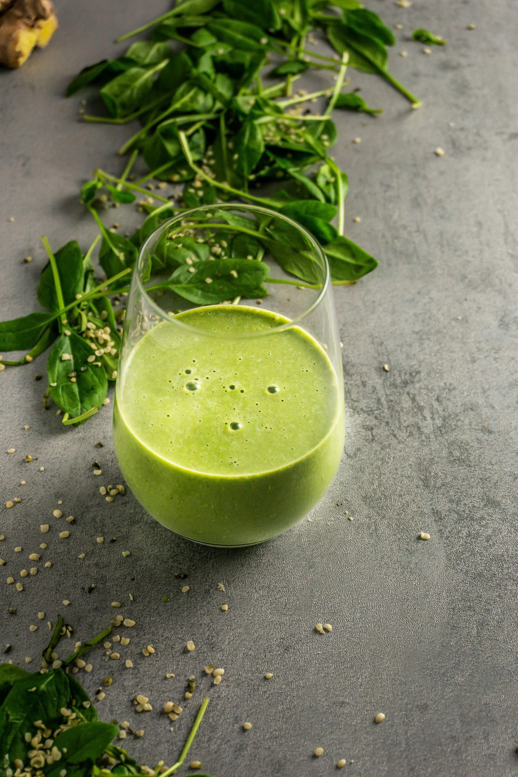 Green Monster Smoothie in a glass on a grey background with scattered spinach and hemps seeds in the background
