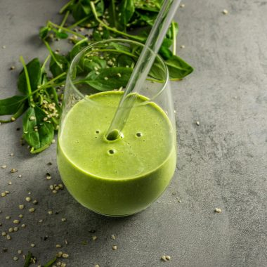 Green Monster Smoothie in a glass with a glass straw. Photographed on a grey background with scattered spinach and hemps seeds in the background