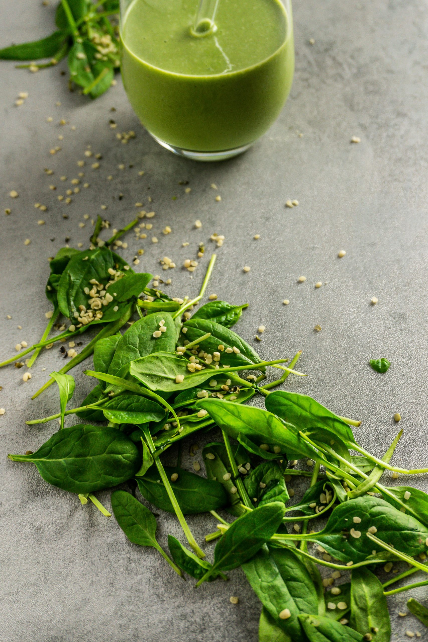 Spinach and hemp seeds scattered on a grey background with a Green Monster Smoothie in the background.