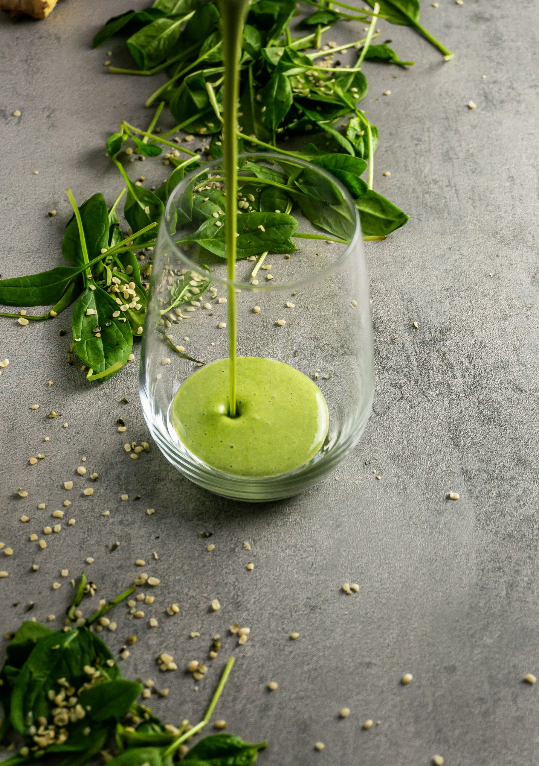 Green Monster Smoothie being poured into a glass. The glass is placed on a grey background with spinach and hemp seeds scattered around