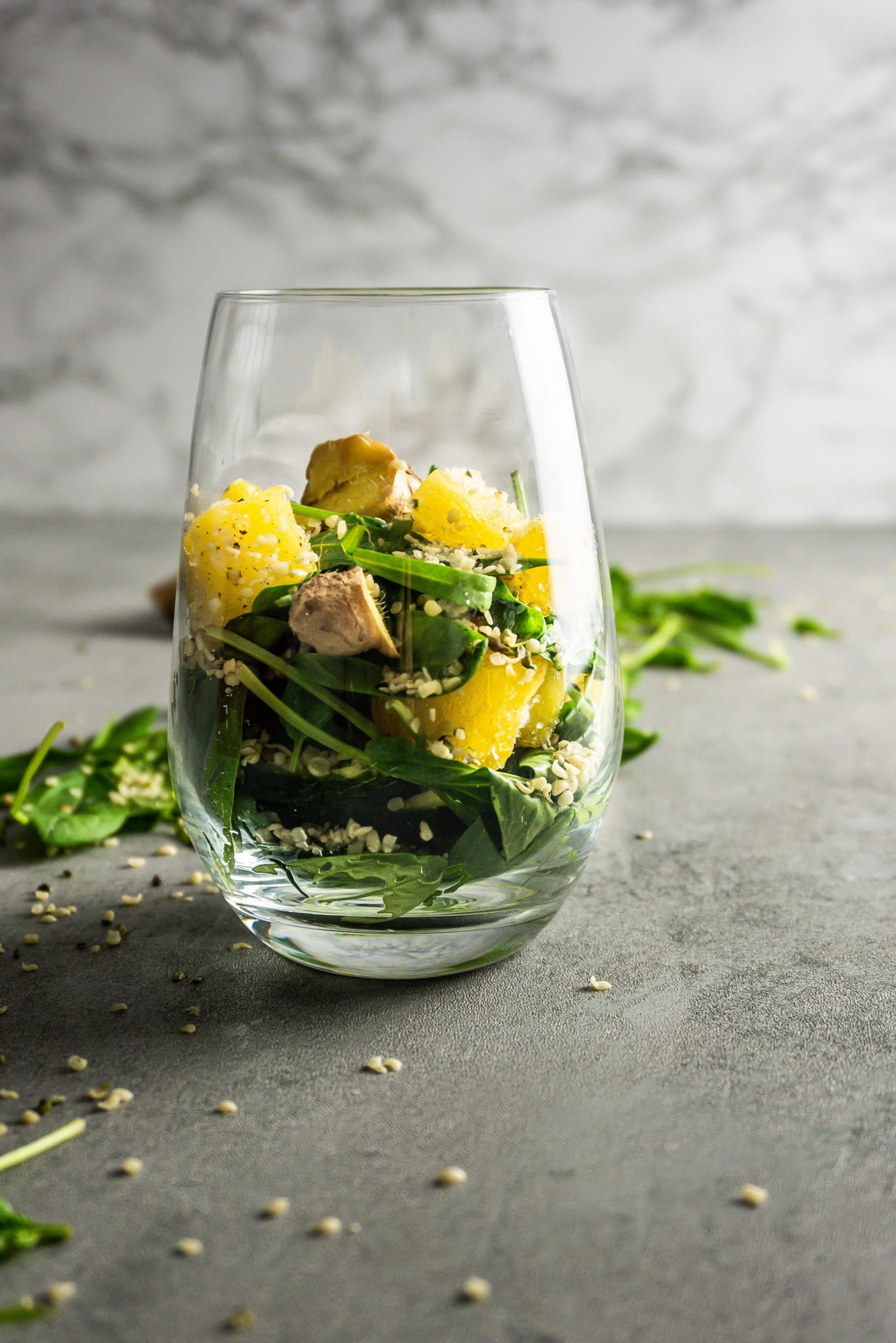 Ginger, pineapple, cucumber, spinach, and hemp seeds in a glass