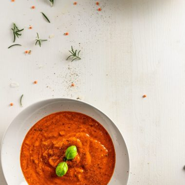 Roasted Red Pepper Soup visible in a bowl with scattered lentils, rosemary, and pepper on a white background