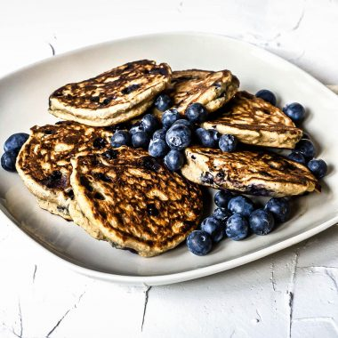 Blueberry Ricotta Pancakes with scattered blueberries on top