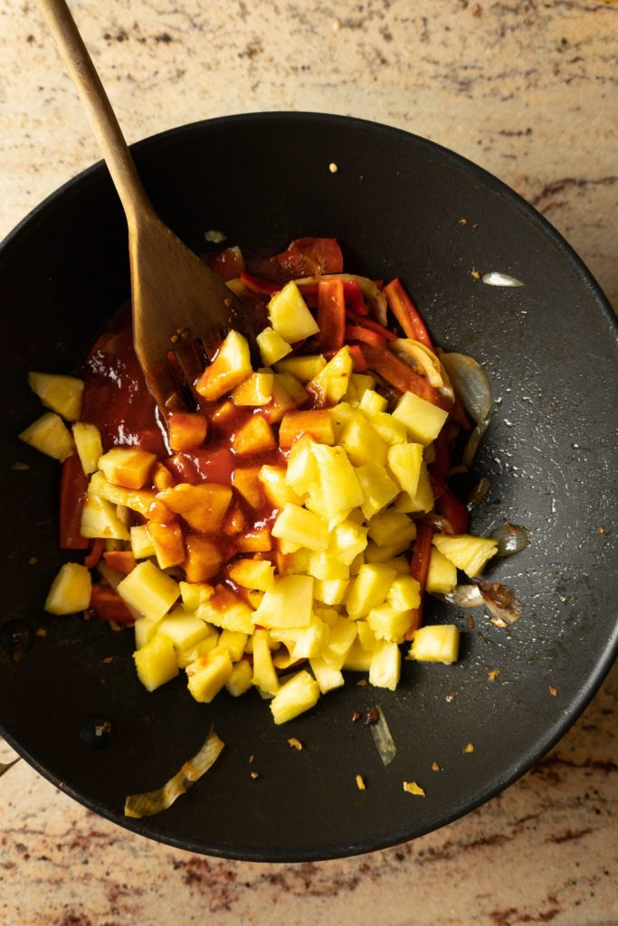Cut up onions, red peppers, and pineapple in a wok mixed with Chinese Sweet and Sour (Sauce)