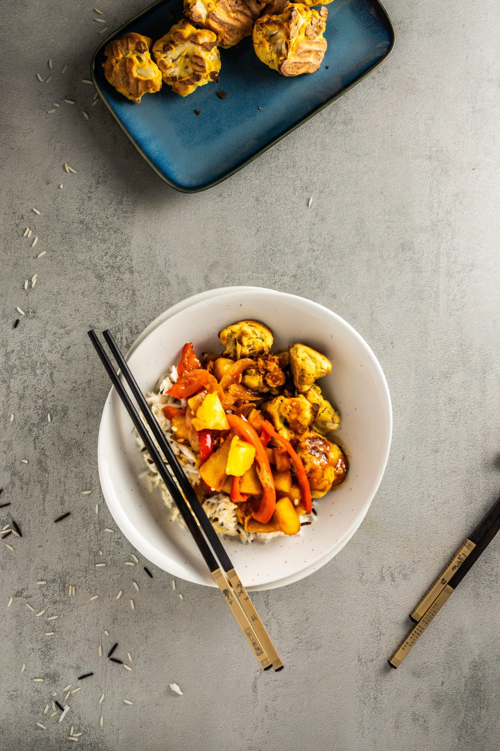 Chinese Sweet and Sour (Sauce) with rice and battered cauliflower, in a bowl with some chopsticks ready for eating