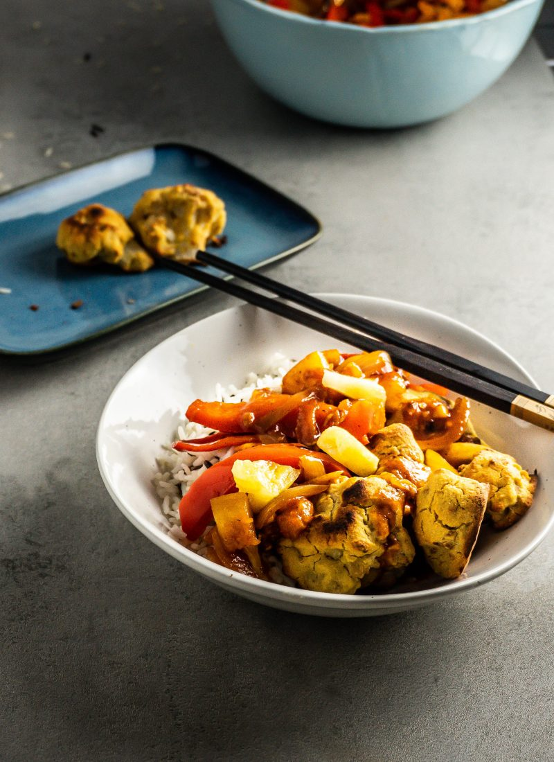 Chinese Sweet and Sour (Sauce) with rice and battered cauliflower, in a bowl with some chopsticks ready for eating photographed from a three-quarter angle