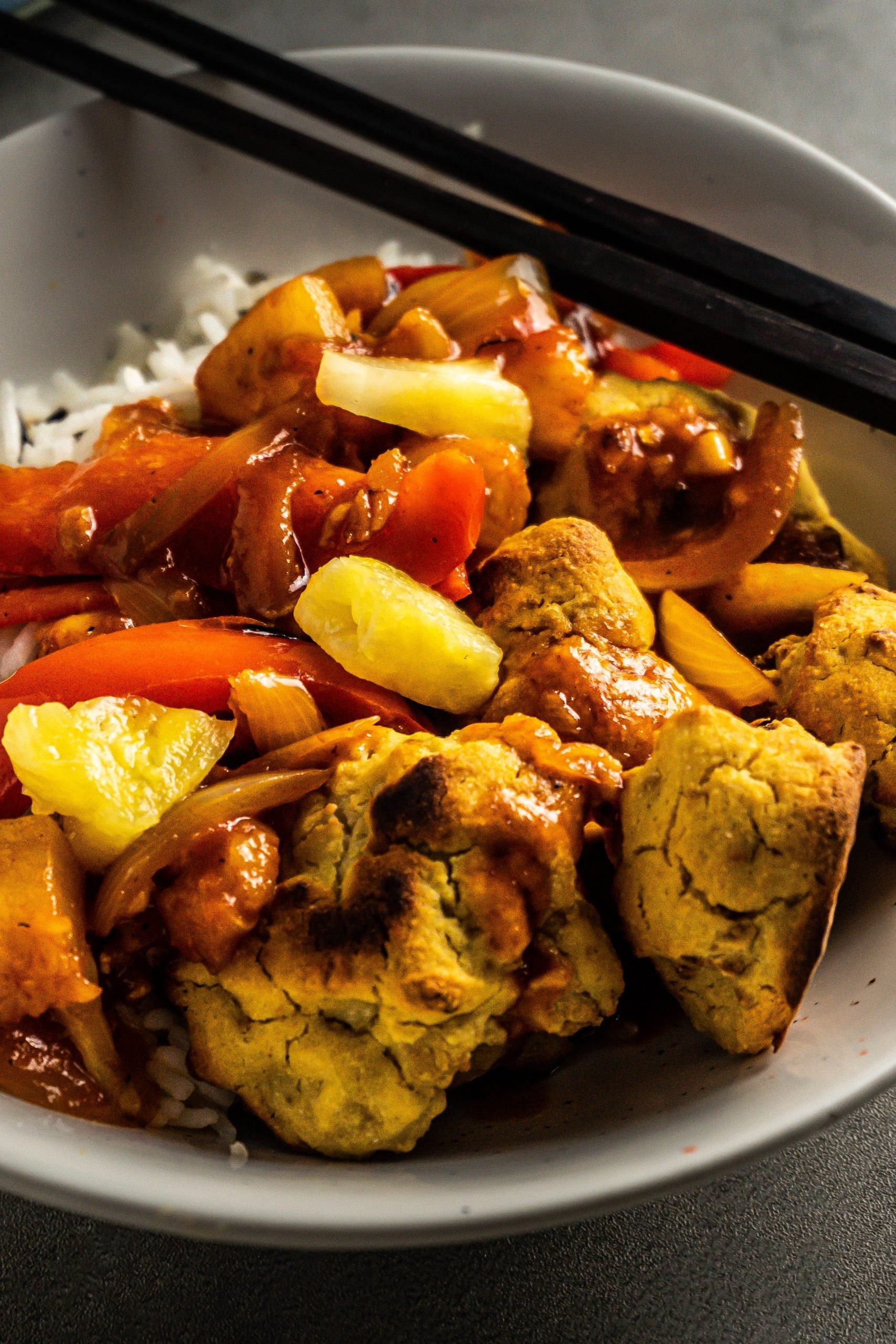Chinese Sweet and Sour (Sauce) with rice and battered cauliflower, in a bowl with some chopsticks ready for eating photographed up close
