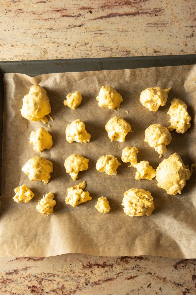 Cauliflower covered in batter on a baking sheet
