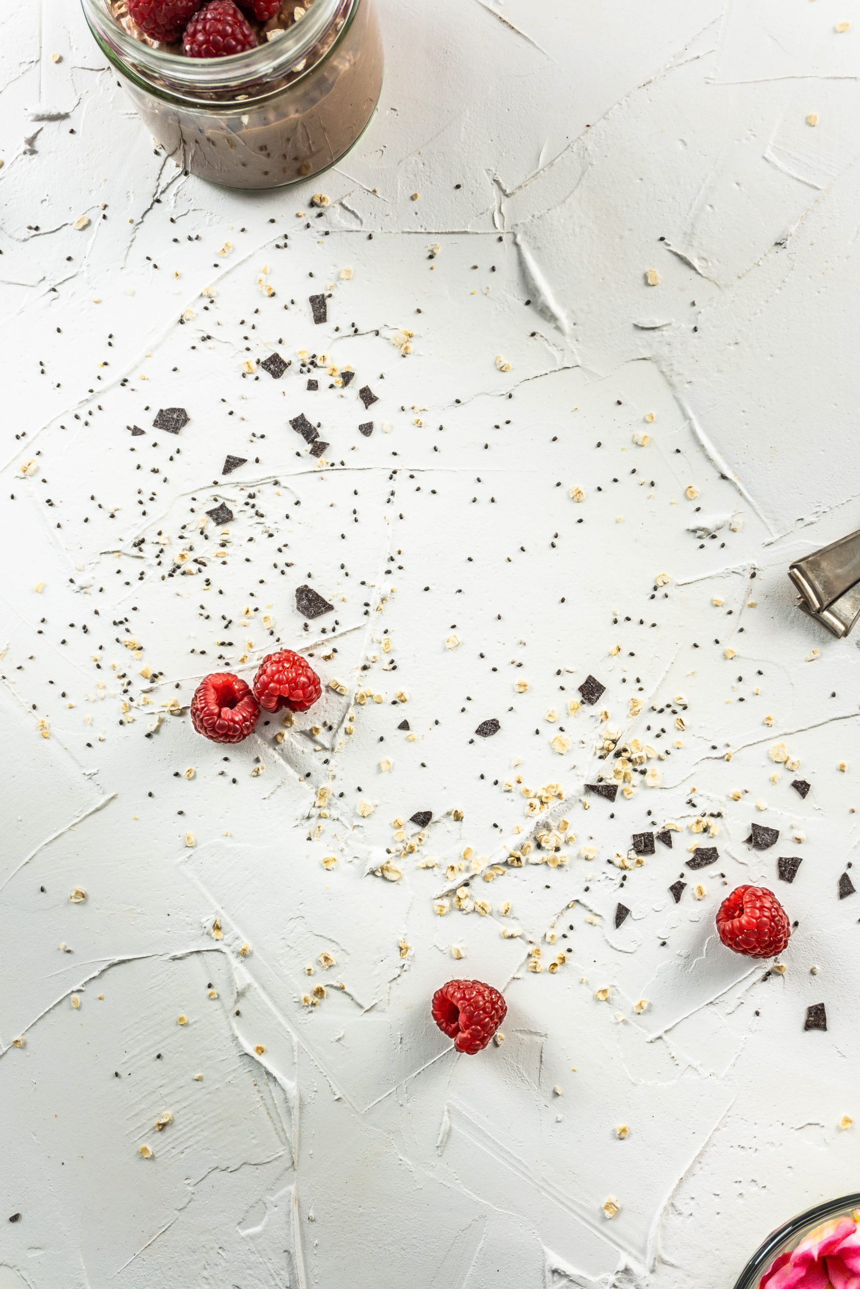 Strewn oats, chia, chocolate, and raspberries on a white background