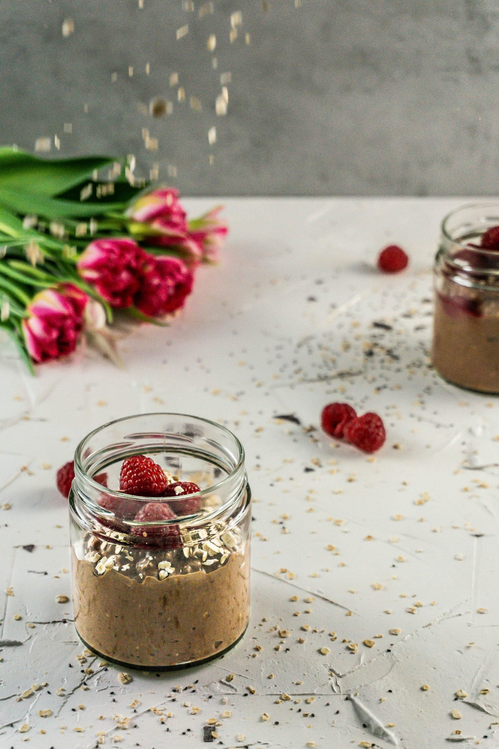 Oats flying through the air on a jar of Chocolate Raspberry Overnight Oats