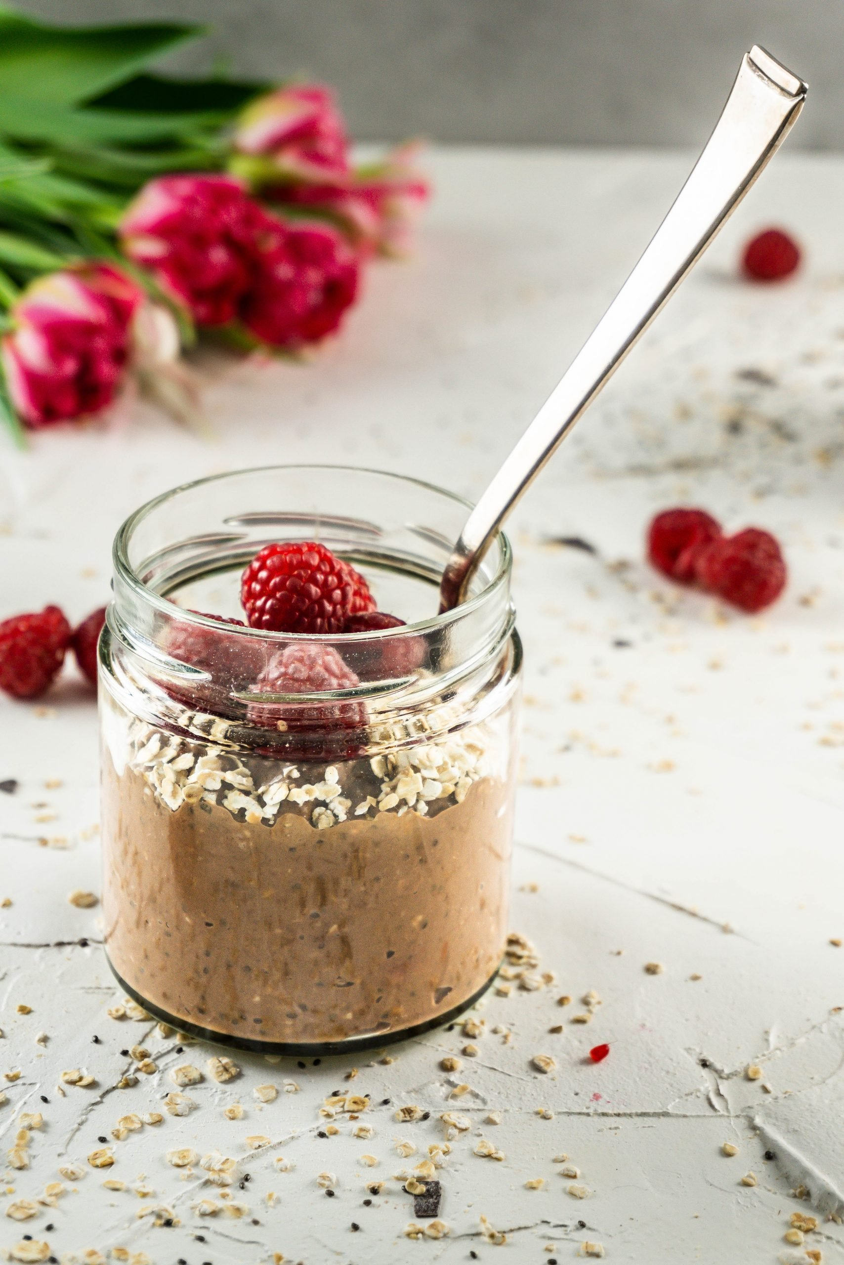 A glass of Chocolate Raspberry Overnight Oats topped with raspberries and a spoon stuck into it