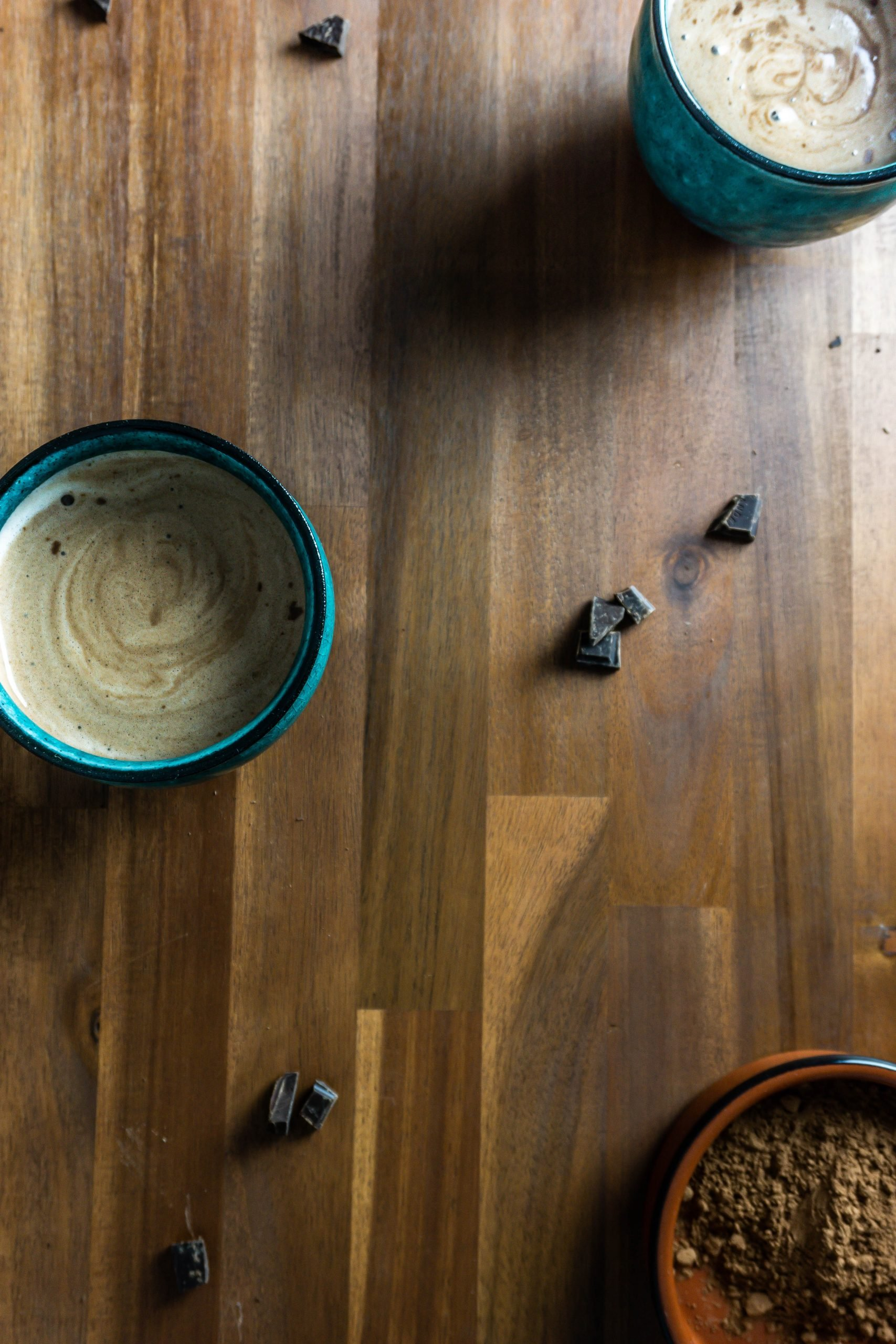 Two Homemade Hot Chocolates on a wooden surface with scattered chocolate and cocoa powder in the background