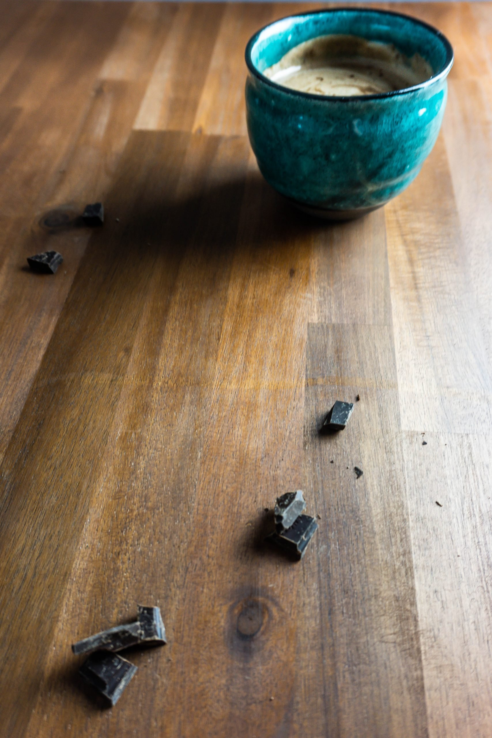 Homemade Hot Chocolate photographed on a wooden surface with scattered chocolate in the front
