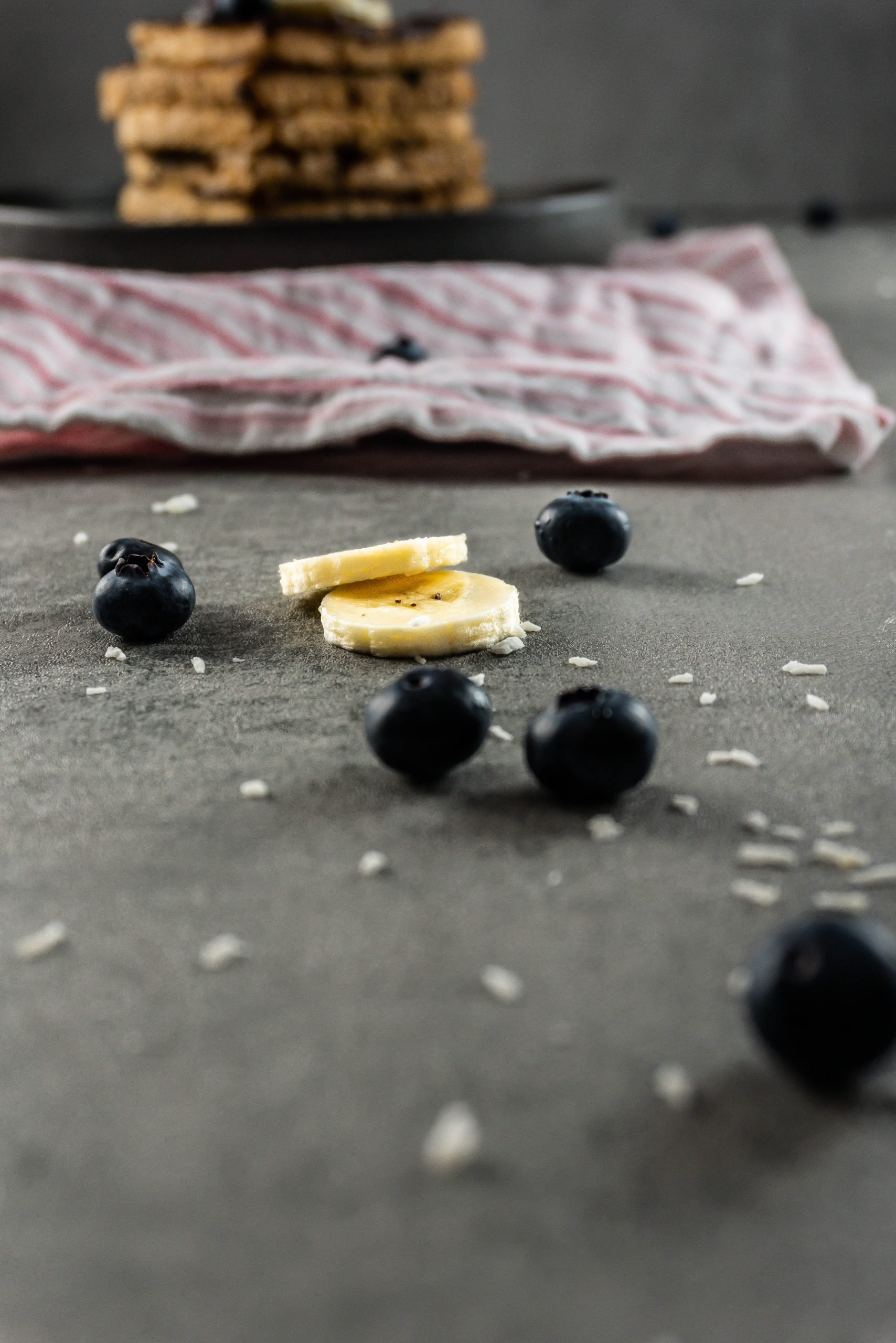 Banana slices and blueberries in focus with a stack of Cinnamon Banana French Toast visible in the back