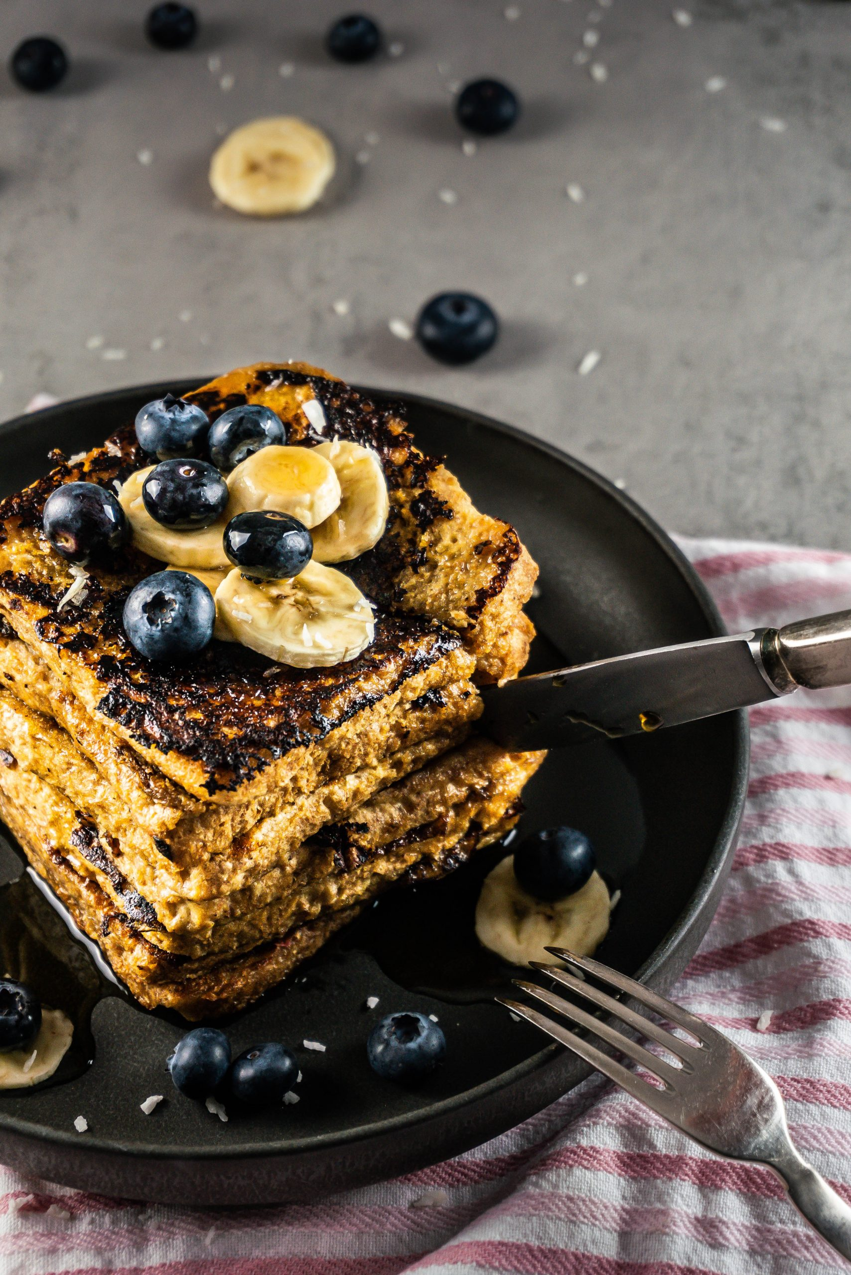 A stack of Cinnamon Banana French Toast covered in maple syrup with a knife cutting into it