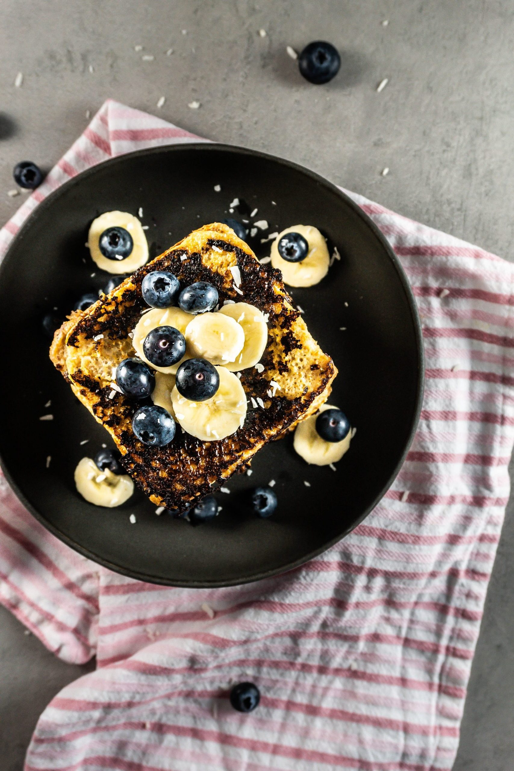 Cinnamon Banana French Toast stacked on top of each other and topped with blueberries, shredded coconut, and banana slices photographed from the top
