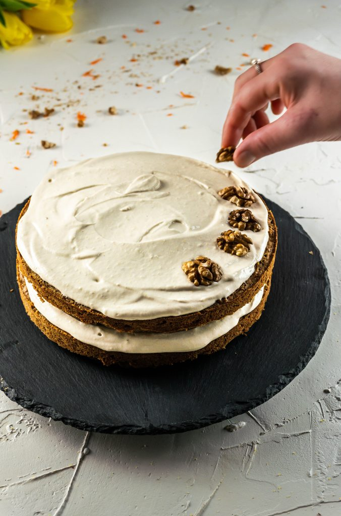 Adding Walnuts on top of the Gluten-free Carrot Cake with a Vegan Buttercream Frosting