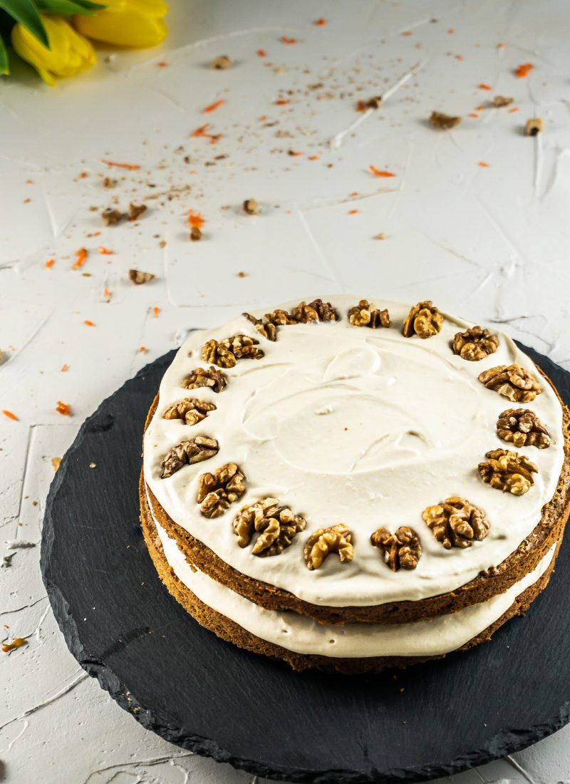 Gluten-free Carrot Cake with a Vegan Buttercream Frosting on a cake plate photographed on a white background with scattered walnuts and carrots visible photographed from above