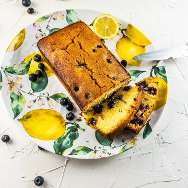 Lemon Blueberry Polenta Bread on a colorful plate with two pieces cut off photographed from above