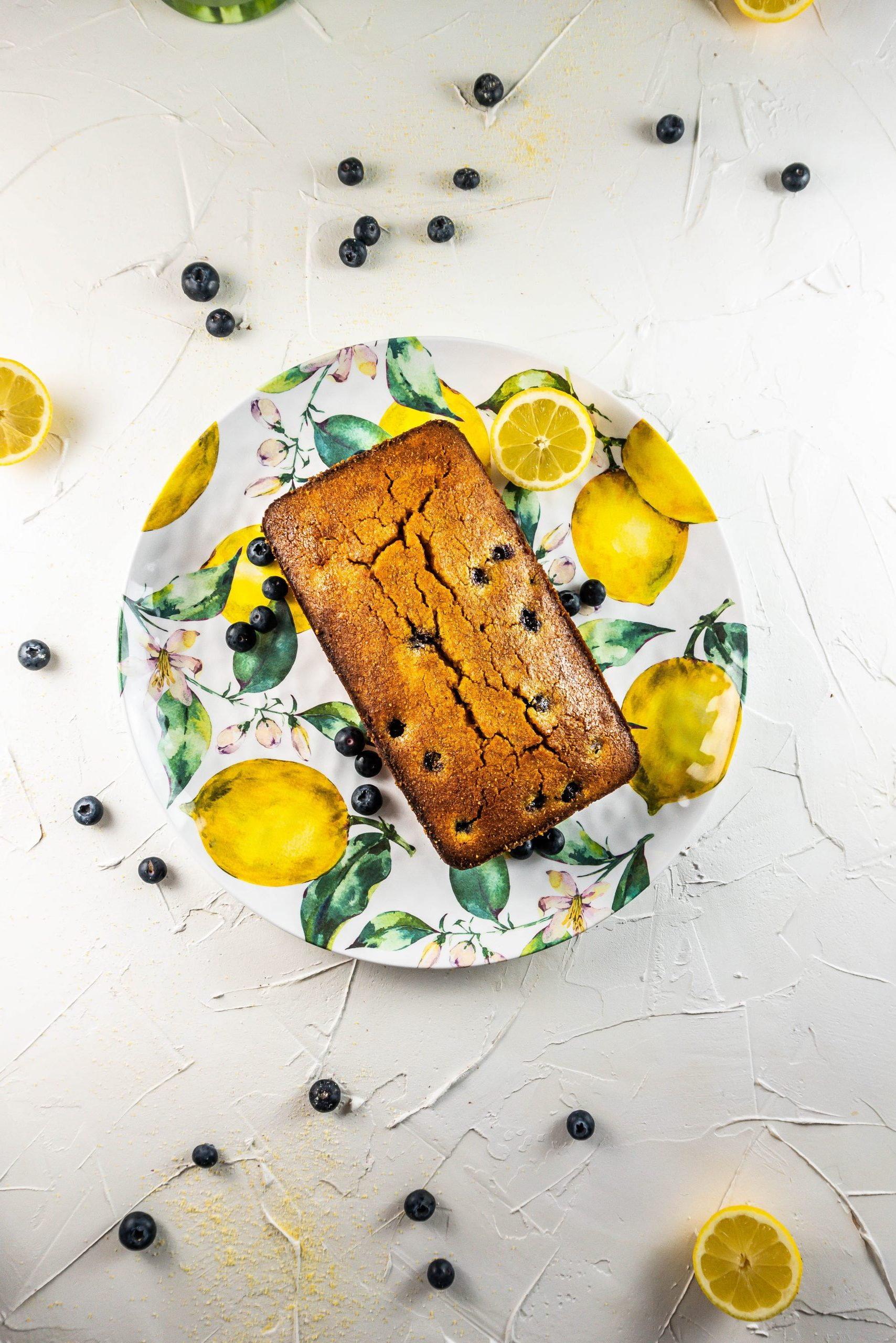Lemon Blueberry Polenta Bread on a colorful plate with scattered polenta and blueberries photographed from above