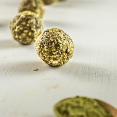 Matcha Green Tea Energy Bites on a white background with oats, cashews, and matcha strewn around photographed from a side-angle