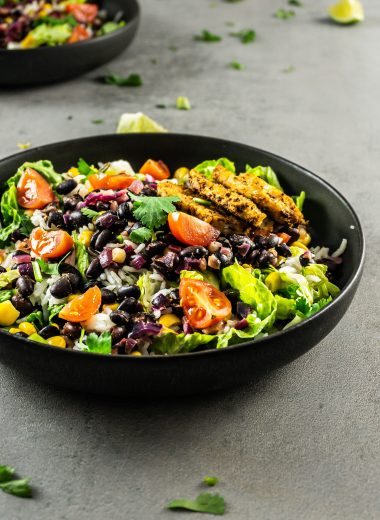 Vegan Burrito Bowl photographed from a three-quarter angel with scattered lime and cilantro visible