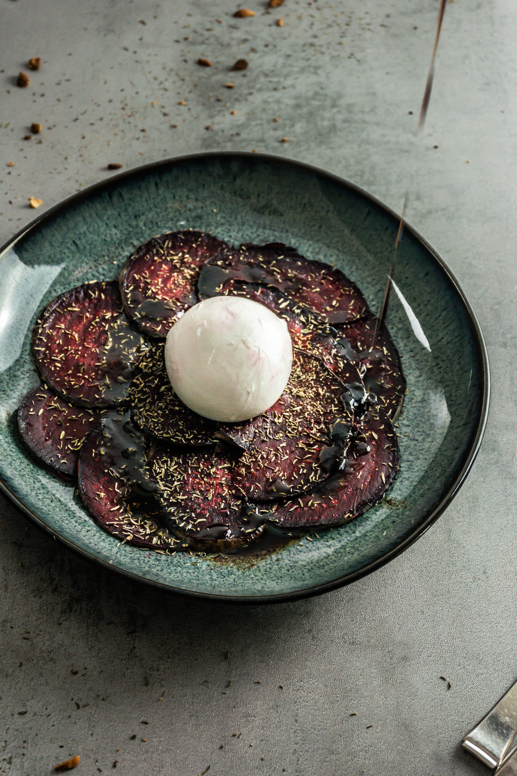 Beetroot Carpaccio with Burrata with sauce being poured onto the plate