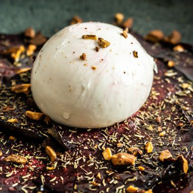 Beetroot Carpaccio with Burrata on top photographed up close