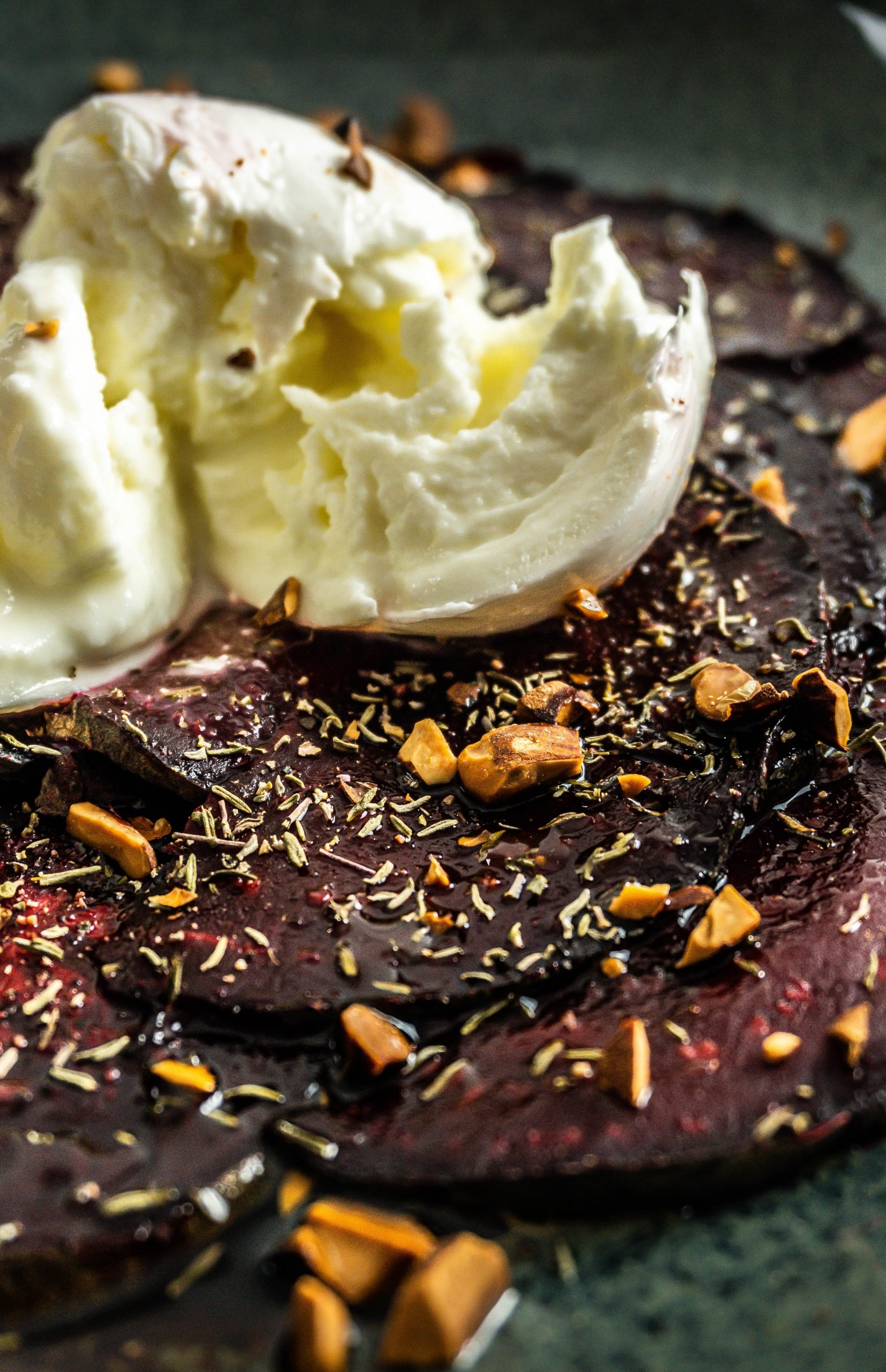 Beetroot Carpaccio with a Burrata split up on top photographed up close