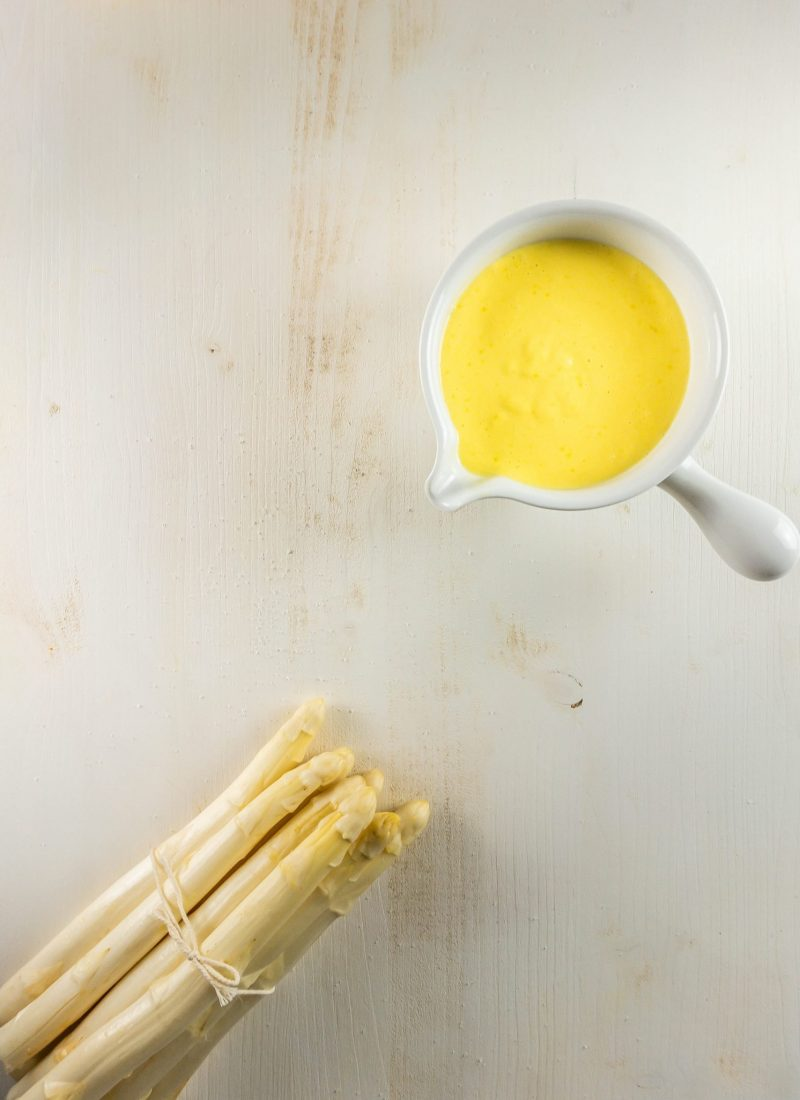 Easy Sauce Hollandaise with asparagus in the picture on a white background photographed from above