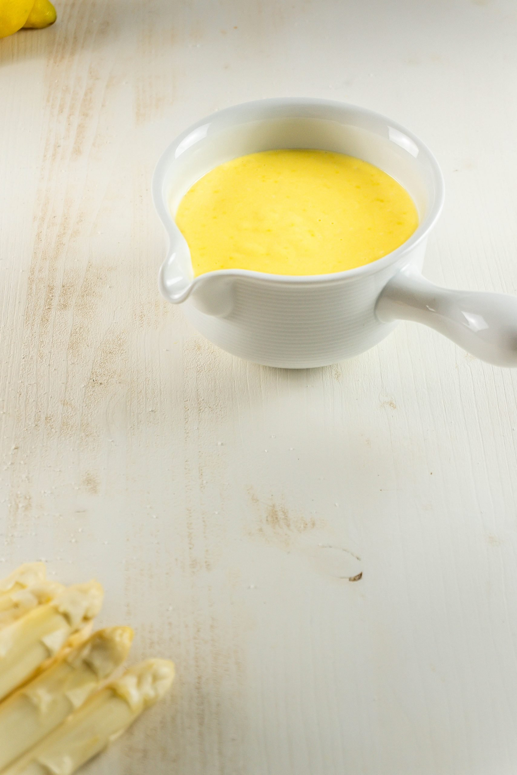 Easy Sauce Hollandaise in a gravy boat on a white background