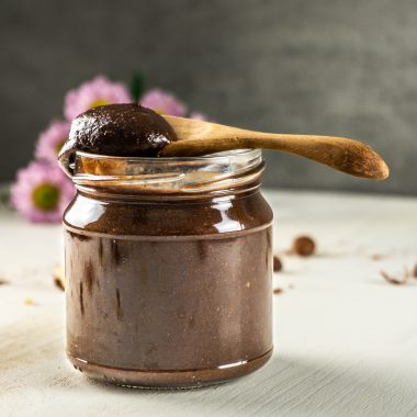 Vegan Nutella in a glass jar with a wooden spoon set on top and with Nutella on it