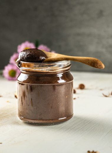 Vegan Chocolate Hazelnut Creme in a glass jar with a wooden spoon set on top and with Nutella on it