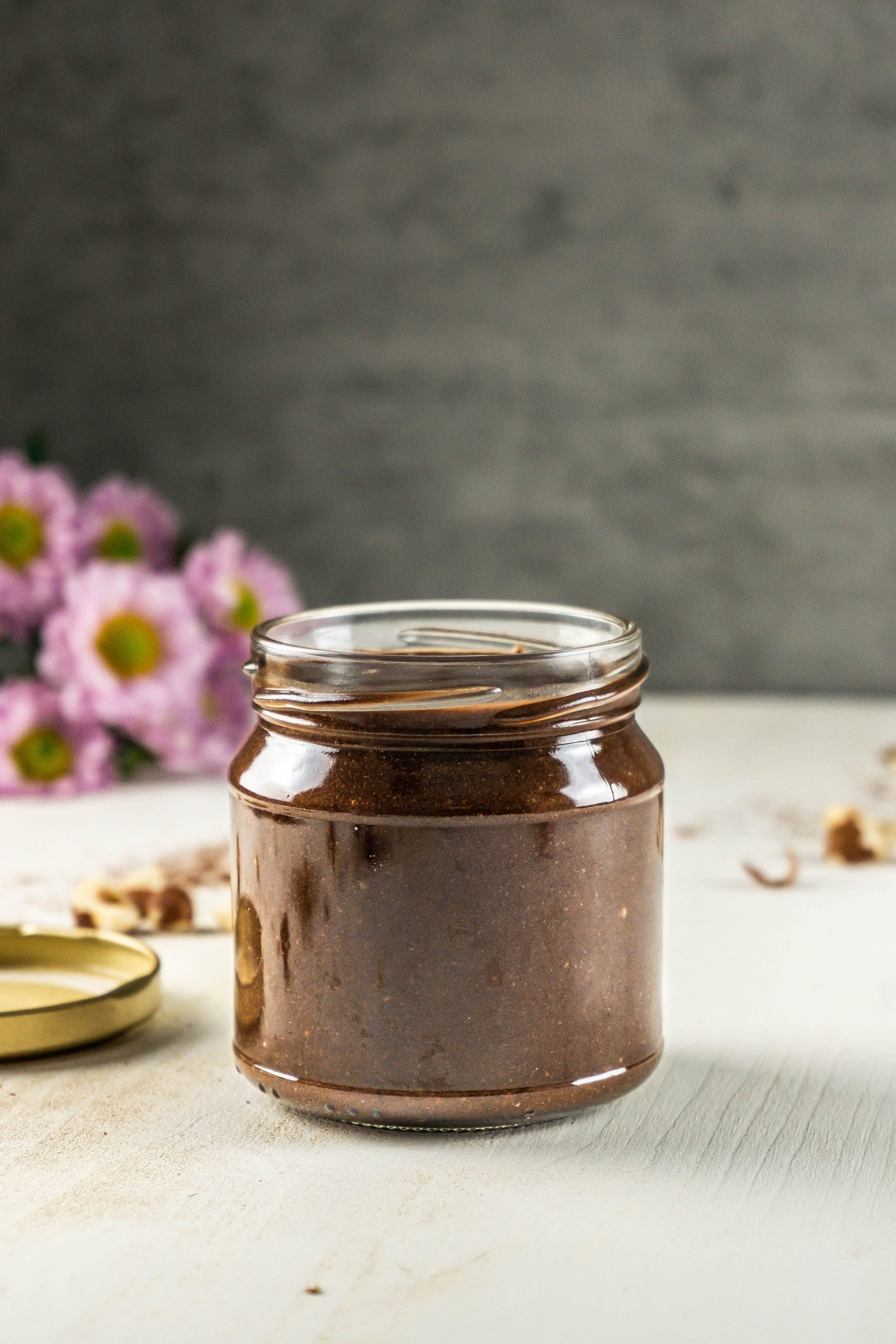 Vegan Chocolate Hazelnut Creme in a glass jar with scattered hazelnuts visible in the background