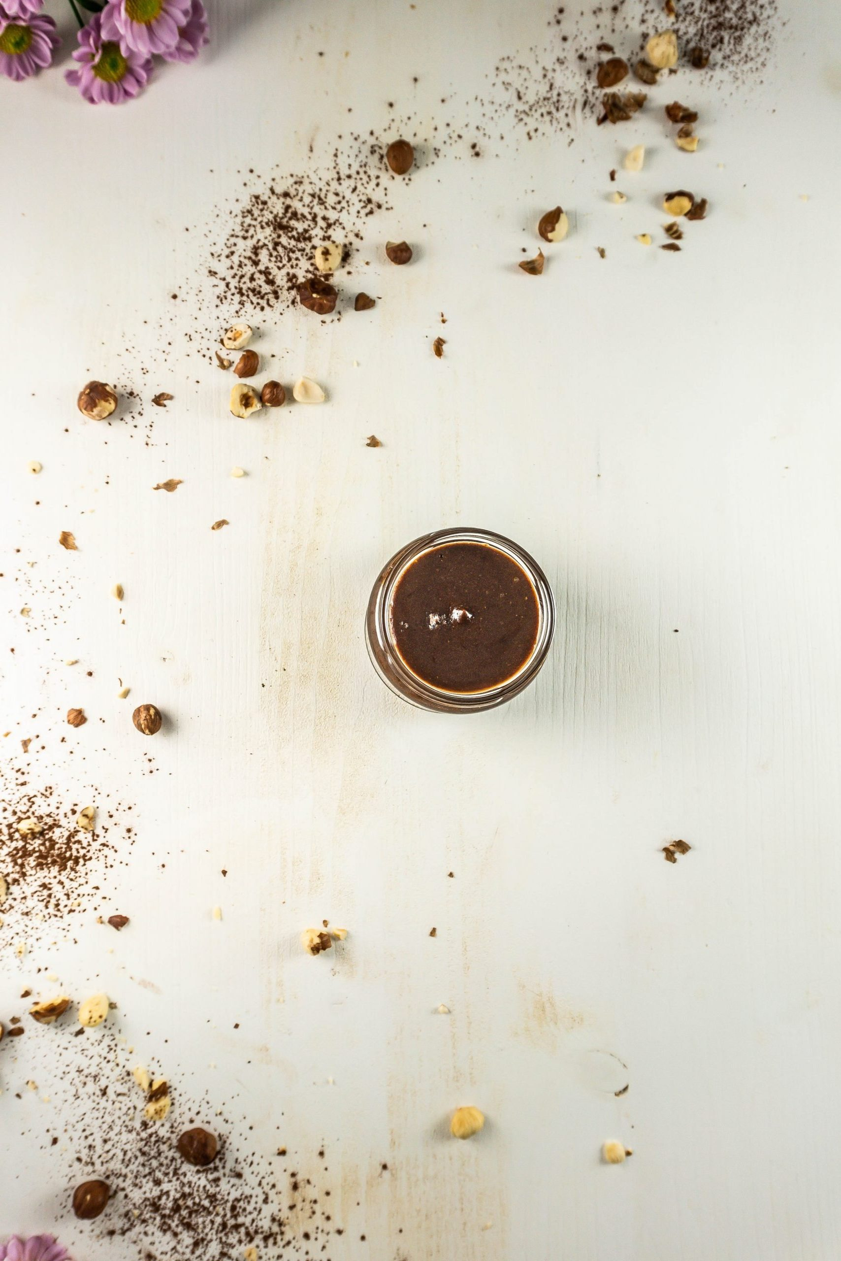 Vegan Chocolate Hazelnut Creme in a glass jar with scattered hazelnuts visible in the background photographed from above