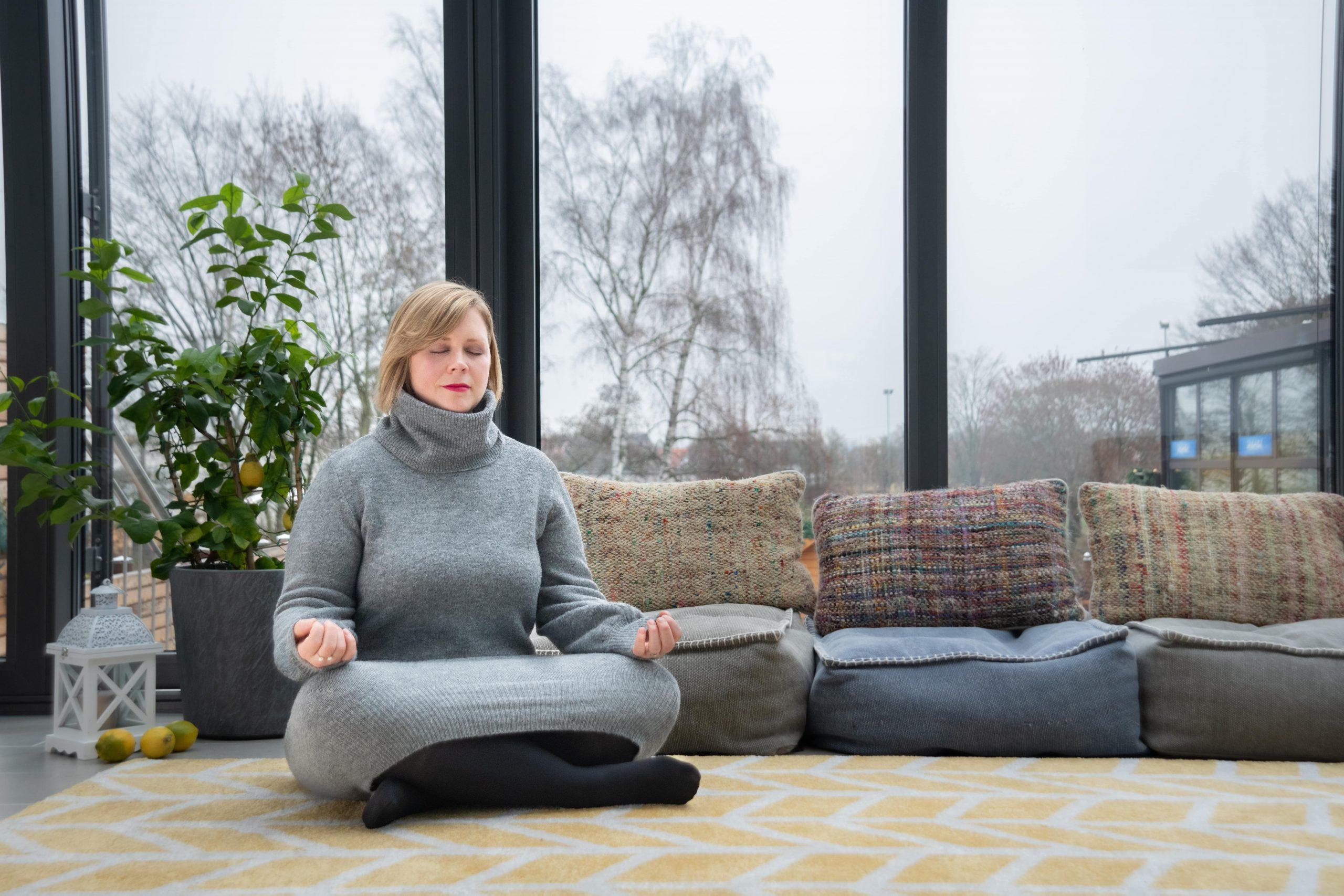 Ann Robejsek sitting in a conservatory meditating