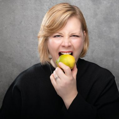 Ann Robejsek biting into a lemon looking aggrevated