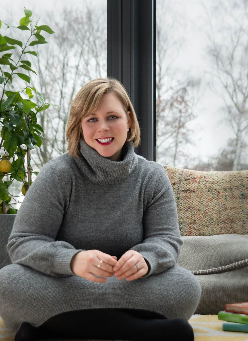 Ann Robejsek sitting in a conservatory smiling at the camera