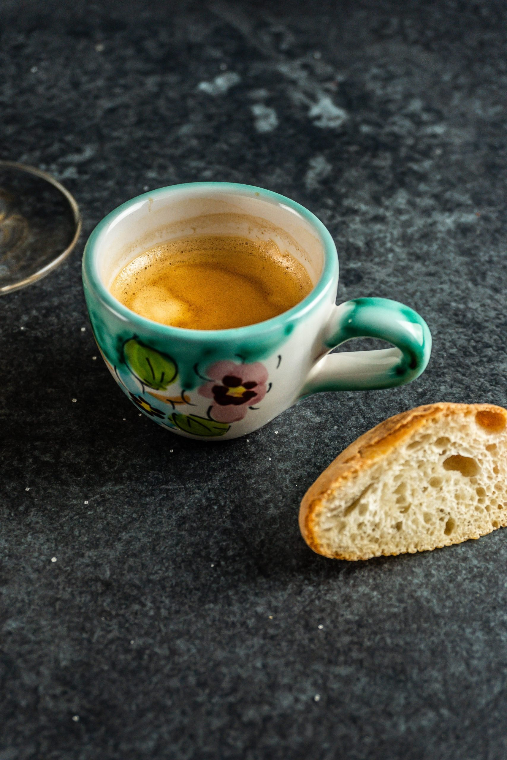 A cup of espresso coffee on a dark background with a slice of white bread visible. Avoiding caffeine is one of the key components in how to combat anxiety - part 1