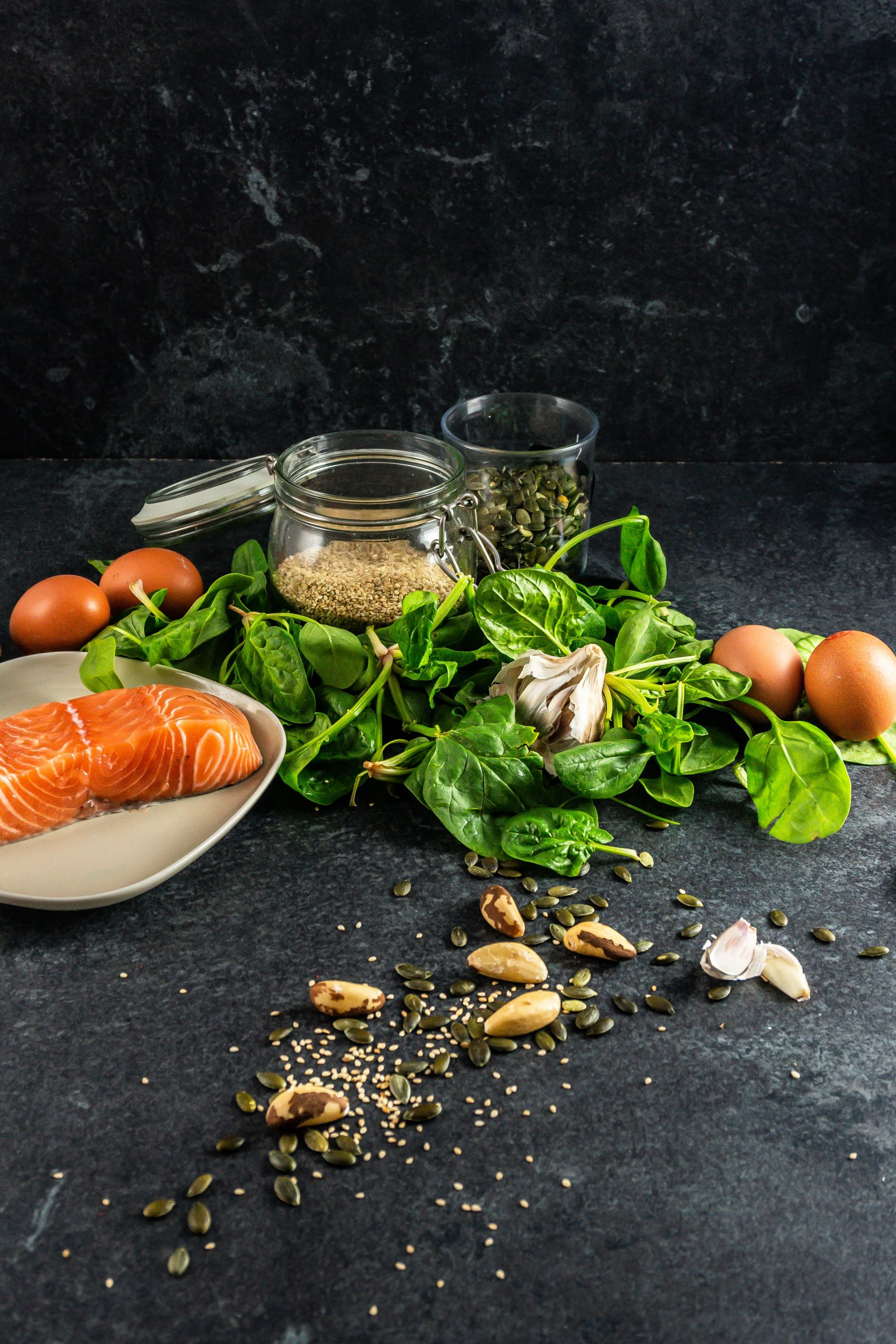 Salmon, eggs, spinach, garlic, and nuts and seeds on on a dark background