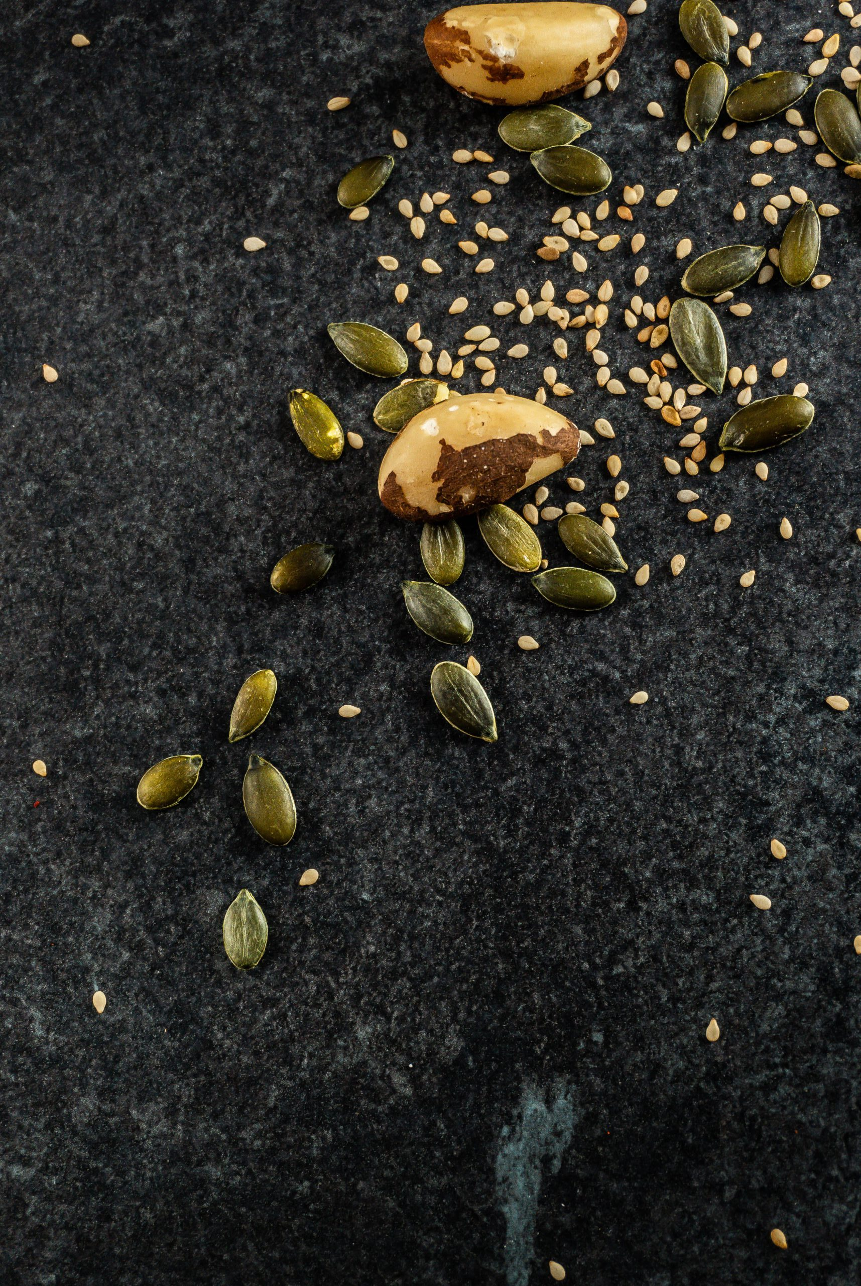 Pumpkin seeds surrounded by sesame seeds and brazil nuts
