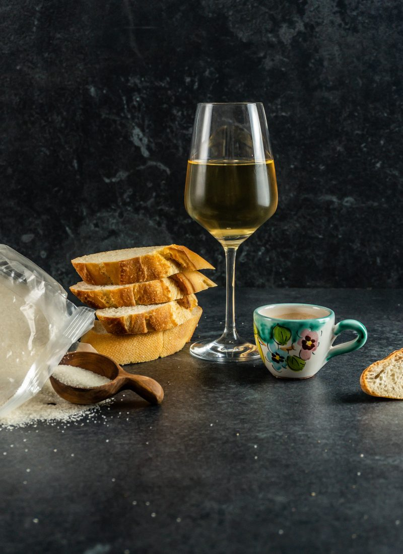 Sugar, a filled wine glass, white bread, and coffee on a dark background