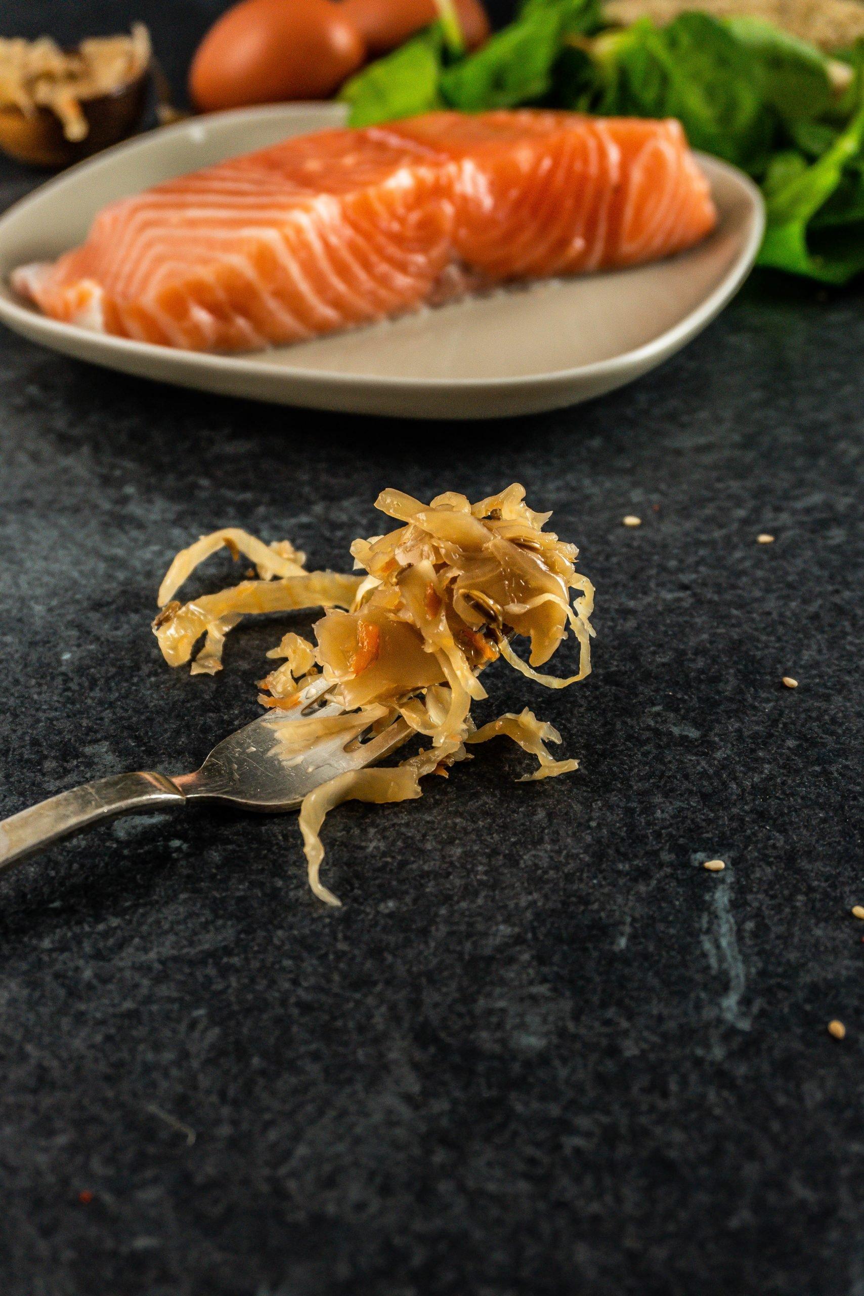 Sauerkraut on a fork laying on a dark background