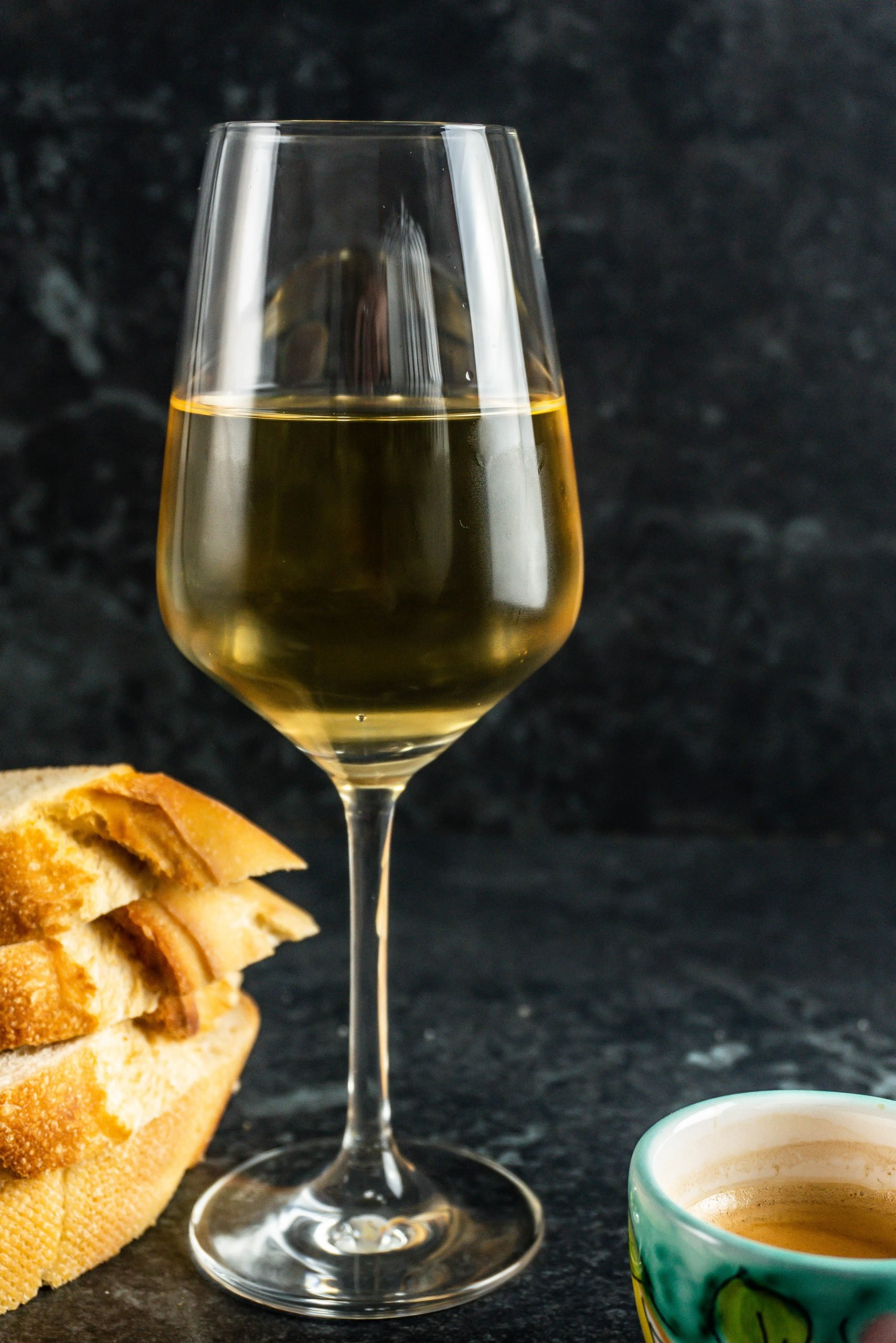 A glass of white wine on a dark background. Avoiding alcohol is one of the key components in how to combat anxiety - part 1